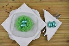 Couvert de table de Pâques de printemps dans le blanc avec le nid vert fait main et les oeufs brillants bleus Photographie stock