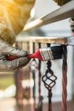 Couvert des balustrades forgées par l'amorce et la peinture, outil de brosse, rotection contre la rouille, déroulement des opérat Images stock