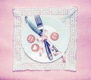 Couvert romantique de table de dîner avec des cartes de décoration et de message de ruban sur le napperon de dentelle et le fond  Photographie stock