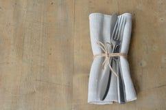 Couverts avec la serviette décorée d'une notation sur un conseil en bois Approprié comme fond photographie stock