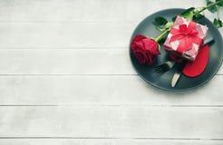 Couverts de cuisine de plat avec le cadeau et la rose de rouge Jour de valentines heureux Photographie stock libre de droits