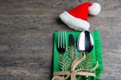 Couverts de fête réglés : couteau, cuillère et fourchette avec le ruban et le tissu vert décorés d'un brin de pin et de petit cha Image stock