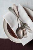 Couverts de vintage, différents plats et nappe brune Photographie stock libre de droits