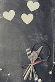 Couverts et coeurs fanés de jour de valentines au-dessus de tableau noir Photos libres de droits