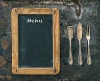 Couverts et tableau noir argentés antiques Type de cru Conce de nourriture photos stock