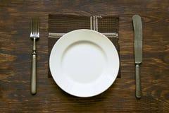 Couverts, plat et serviette sur la table Photographie stock