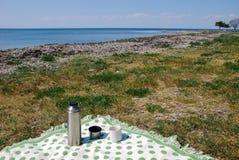 Couverture avec le thermos sur la plage photographie stock libre de droits