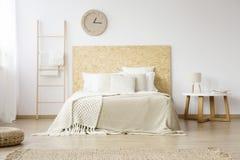 Couverture beige sur le lit blanc photographie stock