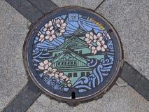 Couverture de drain de trou d'homme sur la rue à Osaka, Japon photos stock