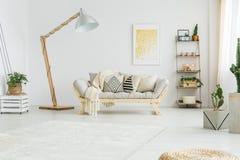 Couverture de lit beige se trouvant sur le sofa gris image stock