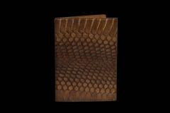 Couverture de passeport de peau de serpent sur un fond noir Photos stock