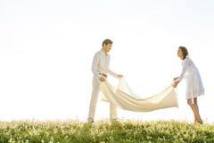 Couverture de propagation de pique-nique de jeunes couples sur l'herbe pendant le jour ensoleillé Image libre de droits