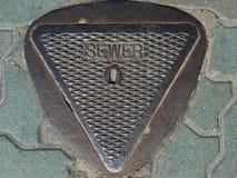 Couverture de trou d'homme d'égout triangulaire photo stock