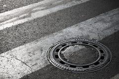 Couverture de trou d'homme d'égout sur l'asphalte foncé Image libre de droits
