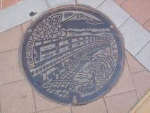 Couverture de trou d'homme dans ÅŒtsuki, Japon Photos stock