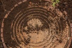Couverture de trou d'homme ronde d'égout en terre urbaine sale Photo stock