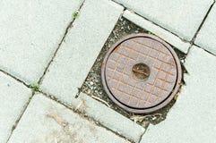 Couverture de trou d'homme rouillée de point d'accès pour une valve coupée à une conduite d'eau principale le long d'un trottoir Image libre de droits