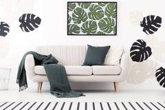 Couverture et coussin verts sur le canapé dans l'interio blanc de salon images stock