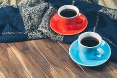 Couverture et deux tasses de café sur le plancher en bois Image stock