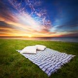 Couverture et oreillers sur l'herbe Images stock