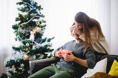 Couverture heureuse d'ami de surprise de jeune femme de couples de vacances de Noël ses yeux Photos stock