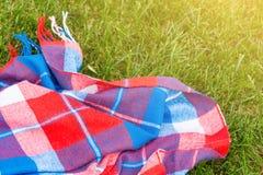 Couverture lumineuse à carreaux sur la pelouse fraîche d'herbe Couleurs rouges, vertes et bleues vibrantes Vue supérieure Copyspa photos stock