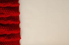 Couverture rougeâtre tricotée sur un fond blanc avec l'espace de copie photographie stock