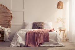 Couverture rouge sur le lit avec des coussins dans l'intérieur blanc de chambre à coucher avec la chaise de lampe et de rotin photographie stock libre de droits