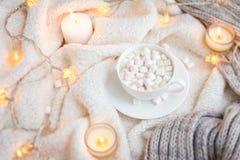 Couverture, tasse de café, guimauves, lumières de Noël, jouet de vintage, bougies Image stock