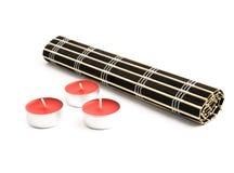 Couvre-tapis roulé de bambou noir et trois bougies rouges Photographie stock libre de droits