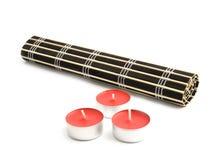 Couvre-tapis roulé de bambou noir et trois bougies rouges Photos stock
