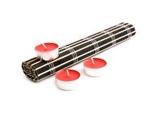 Couvre-tapis roulé de bambou noir et trois bougies rouges Photos libres de droits