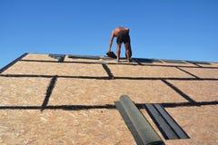 Couvrir la construction de bardeaux de roofer et d'asphalte, tuiles de toiture dans des ses mains Couvrir le concept de construct photos stock