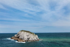 Covachos island in Lencres, Cantabria, Spain. The picture represents a landscape of the Cantabrian coast, Covachos island in Liencres. The sea, blue cloudy sky Royalty Free Stock Photography