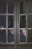 COVARRUBIAS, BURGOS, SPAIN – MAY, 1978. Three old women seen through the window of his house, what happens on the street of a Castilian village on May, 1978 Stock Photos