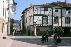 COVARRUBIAS, BURGOS, SPAIN – OCTOBER, 1978. A group of elders talk in the arcades of the square of the medieval village located in the Sierra de France  on Stock Photos
