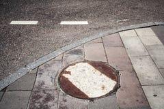Covata arrugginita della fogna vicino alla strada urbano, fondo immagini stock