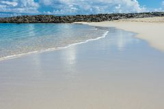 Cove in the Caribbean. A beautiful sandy beach with the turquoise ocean surf soaking the sand Stock Images