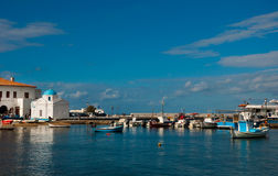 Cove of Mykonos town with fishing boats and church Royalty Free Stock Image