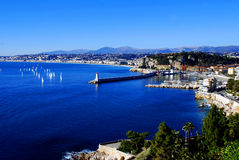 Cove of Nice with floating yachts. Blue sea in the bay with yachts floating on the background of the city and mountains Stock Photography