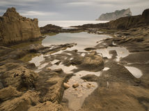 Cove with pools. Rocky beach with some little pools on the foreground and a mountain on the background Royalty Free Stock Images