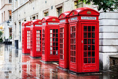 Covent Garden phone boxes. Five British red phone boxes in a row. A line of phone booths in Covent garden after the rain Royalty Free Stock Photography