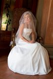 Cover Bride. Bride sitting down with veil over her head Royalty Free Stock Image