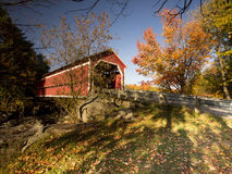 Cover bridge surrounding by the colorful foliage. Covered bridge in Quebec during autumn royalty free stock photo