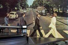 Cover of the famous Beatles Abbey Road album with a turntable in the foreground. royalty free stock photo