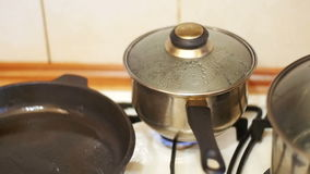 The Cover Moves away from the Pressure of Steam in the Pan of Food on the Stove Home Kitchen. Slow Motion stock footage