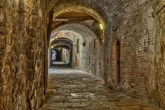 Covered alley in Colle di Val d'Elsa, Tuscany, Italy. The picturesque covered alley Via delle Volte, a medieval dark passage, in Colle di Val d'Elsa, Siena Royalty Free Stock Images