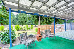 Covered back deck with outdoor seats and fire pit Stock Photography