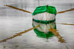 White Boat Reflection. Small white boat covered with green tarp with reflection in the water and five mooring lines attached Royalty Free Stock Image