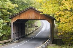 Covered Bridge. A wooden covered bridge in autumn.  Two lane road goes through, with leaves and foliage on both sides in autumn colos of gold and green.  Room Stock Photography
